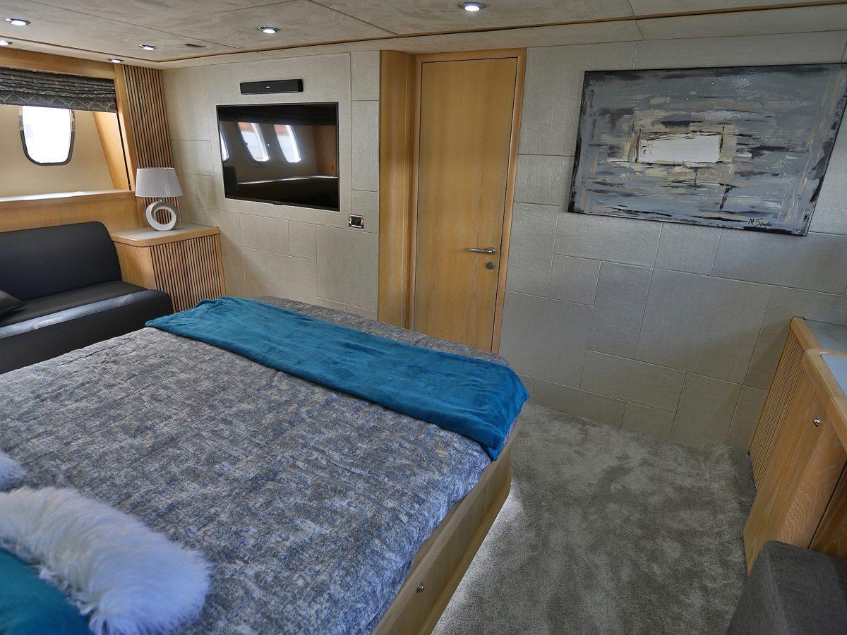 chambre propriétaire avec lit king size, écran plat au mur et décoration chic
