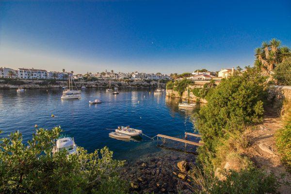 village blanc de minorque, avec la mer et des bateaux