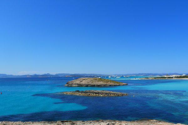 plage d'Ibiza avec des petites îles et la mer turquoise et bleu