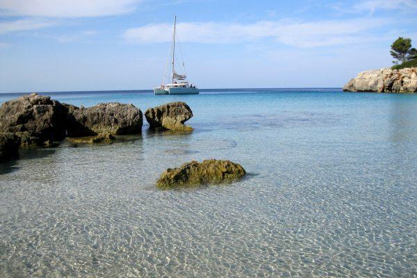 plage avec une eau bleu transparente et un catamaran blanc