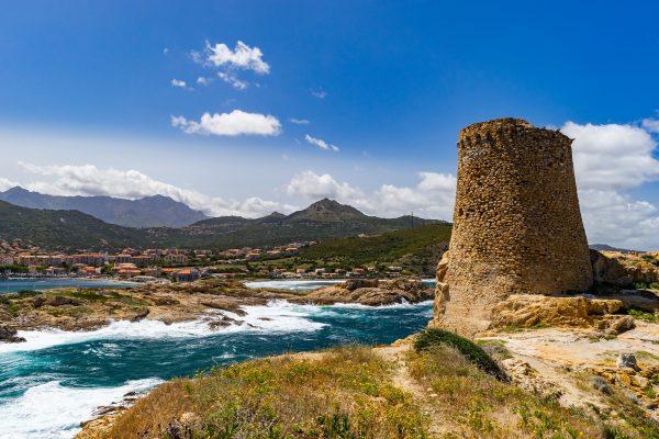 une tour de pierre au bord de la mer et un village au loin