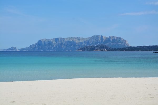 plage de sable blanc, eau turquoise et montagne
